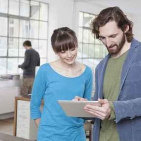 Zwei Kollegen in einem kreativen Bro mit Tablet-PC